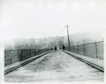 A horse-drawn carraige and people are crossing the South Park Bridge in Morgantown, West Virginia.