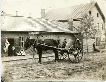 'The Water Works - hauling water supply to High Street on Walnut Street.  Left is James Arthur Garfield Edwards. Right is Charles Daniel Edwards,[sons of John Edwards, owner the water supply business], identified by Grace Edwards Waters.'