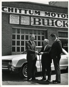 Image taken in fall of 1964; O. S. Chittum, owner of the Buick dealership, standing in center; other two men are Buick officials from the Pittsburgh zone office.