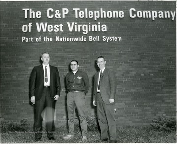 From left to right: Stan Stancowicz, John Morgan, and Howard Husk standing under  sign that reads: The C and P Telephone Company of West Virginia, Part of the Nationwide Bell System.  Morgantown, W. Va.