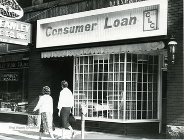Consumer Loan office located in Morgantown, W. Va. Pedestrians passing by, walking down the street. O.B. Fawley Music Company to the left of Consumer Loan