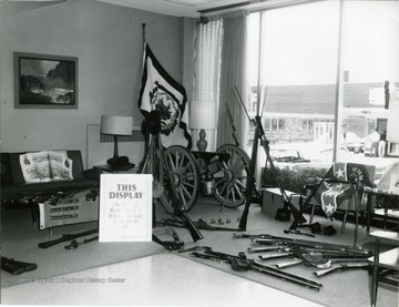 Types of weapons and equipment used during the Civil War, including rifles, banonets, a cannon and ammunition are displayed.