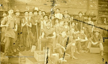 Anton Romisch, second from left standing. Workers pose for photograph. Many of the workers holding tools.