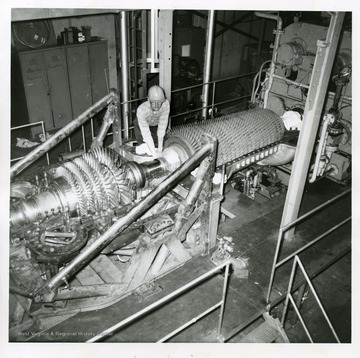Coal Research Bureau (Bureau of Mines). Charles N. Resenecker of the Bureau's gas turbine staff checks assembly of the bearing between the turbine and compressor rotors. The large bladed rotor at the left contains the new blades, and is the heart of the gas turbine plant. The air compressor is the bladed unit at the right. Hot high-speed gases from the combustion of coal spin the rotor at the left and then leave through an exhaust stack (not shown). The air compresor, rotated by the turbine, supplies air needed to burn the coal. The turbine also drives electric generators (not shown in this photograph).