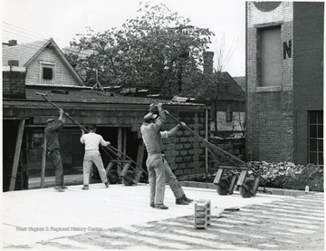 Four men working on the construction of Massulo's Dry Cleaners on High Street, Morgantown, W. Va.