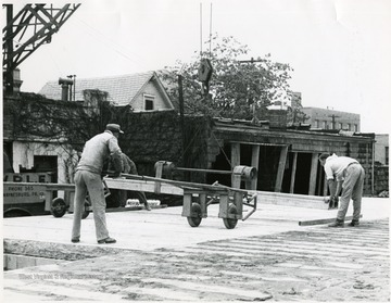 Three men working on the construction of Massullo's and the Mountaineer Sport Shop building on High Street, Morgantown, W. Va.
