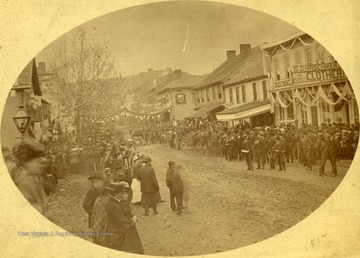 Parade on High Street in Morgantown, W. Va. Crowds flood the dirt-road. Horse-drawn carriages are seen amongst the crowd.