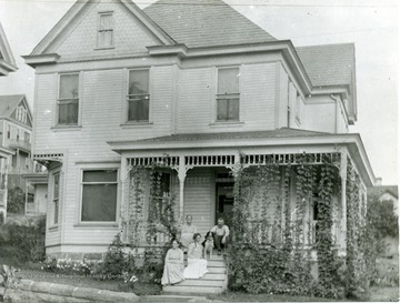 Home on Spruce Street in Morgantown, W. Va. People, possibly a family, sit on the front porch and steps with their dog.