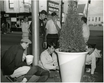 Male students painting a planter on high street.