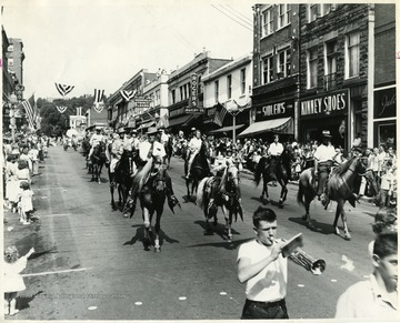 People on horses ride down High Street for a parade.