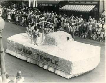 Three women in dresses ride the Labor Temple float.