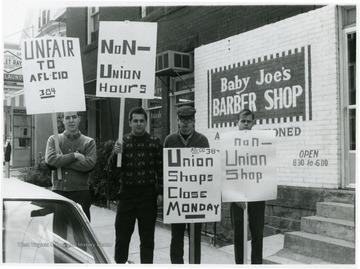 Members of the AFL-CIO 384 with signs picketing Baby Joe's Barber Shop