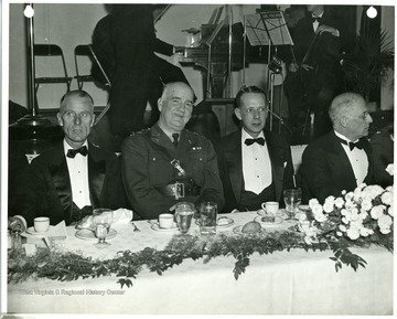 'Major General Charles T. Harris, Jr. Ordnance Department, Washington D.C., was the guest of honor at banquet held in Hotel Morgan, Morgantown, West Virginia. November 17, 1941 at conclusion of defense day celebration. Pictured left to right at the speaker's table are: Lt. Col. W. R. Orton, commandent of the cadet corps, West Virginia University; Major General Harris; Robert G. Wilbourn, President, Morgantown Chamber of Congress and toastmaster at the dinner and Judge Herschel H. Rose of the West Virginia Supreme Court, one of the principal speakers.'