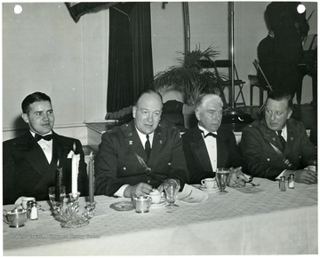 'Among the guests of the Morgantown Chamber of Commerce at the defense day banquet held Nov. 17, 1941 in Hotel Morgan, Morgantown, W. Va. were the four representatives of the War Department and the duPont company pictured above.  Left to right are:  J. A. Grady, field project manager who was in charge of construction for E. I. duPont de Nemours and Co.; Major Alexander P. Gates, contract information section, construction division, Office of the Quartermaster General;  S. K. Varnes, Chief Engineer, and Major Fred O. Mitchell, Deputy Zone Constructing Quartermaster, Columbus Ohio.'