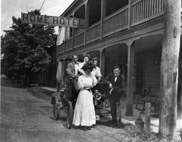 A man and a woman are standing in front of an automobile that is parked in front of the Home Hotel in Morgantown, West Virginia. A man and two women are sitting in the automobile.