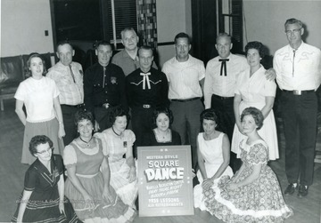 Group portrait of members of the Western Style Square Dance Club in Morgantown with a poster announcing their meeting time and place.