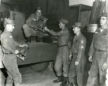 Men in the National Guard unloading equipment from a truck.