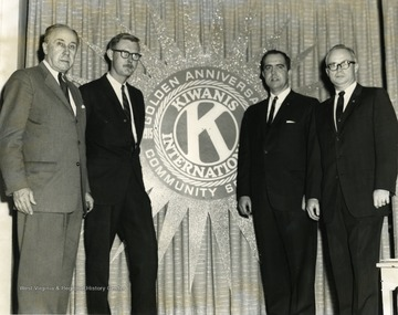 Members of the Kiwanis Club stand near the Golden Anniversary Seal. Members include from left to right: 'Arthur Buehler, Edward V. McMichael, Foster Mullenax, and Don Bond.'
