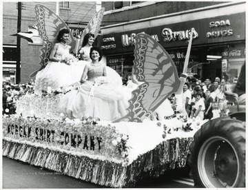 Three ladies in white dresses ride on the Morgan Shirt Company float.