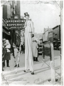'Russell L. Long, Morgantown, W. Va. on high stilts, walks 3 to 4 hour periods on them.  This picture taken on High and corner of Pleasant Street - My construction of my stilts and the foot pivot is my own invention and makes it possible for me to move with comparative ease being a mechanical tall-man the hours I perform on them.  My leg stilts allow me to spread and stoop to go through doors from the sidewalks stilting indoors, and come out again on the sidewalk.  Many business places I have done stilting inside.'