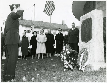 Group of people stand next to a monument with a plaque on it.