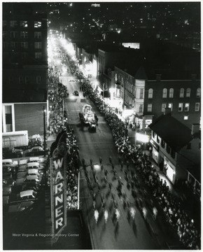A parade goes down High Street at night in Morgantown, W. Va.