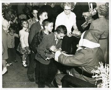 Children are waiting in line to visit with Santa Claus.