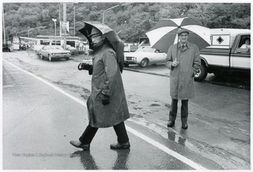 Two men with umbrellas stand on the road.