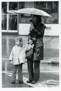 Woman with an umbrella holds the hand of a small girl.