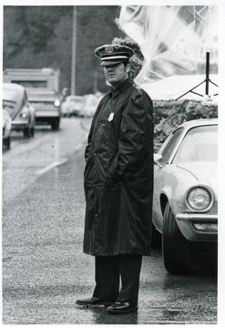 Police officer, Ralph D. Chapman, stands next to the road.