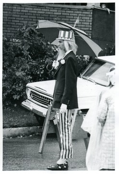 Man dressed as Uncle Sam holds an umbrella and watches the parade.