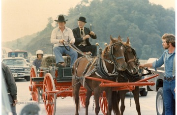 Two horses are pulling a wagon with two men during the Monongalia County Bicentennial Parade in Morgantown, West Virginia.