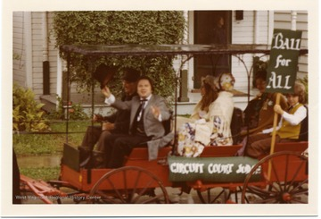A horse drawn wagon in pulling people advertising Ball for Circuit Court Judge during the Monongalia County Bicentennial Parade in Morgantown, West Virginia.