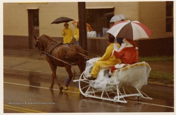 Santa and another man are riding in a horse drawn sleigh during the Monongalia County Bicentennial Parade in Morgantown, West Virginia.