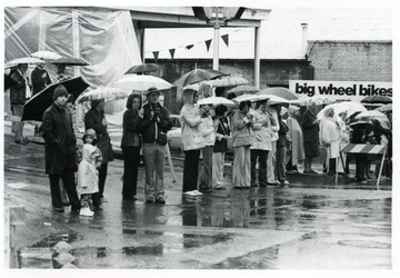 People watch the parade from under their umbrellas.