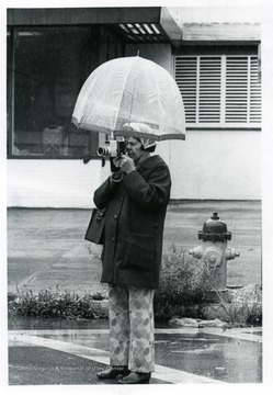Woman with an camera takes a picture from under her umbrella.
