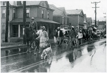 People are riding horses next to people walking their dogs down the road.