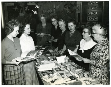 'Bookfair, 1960, Morgantown, W. Va. Decoration - Motto:  fish.  Arranged by committee, including ?. G. Plant.  Plant's own fish on picture. Pat Engle is 3rd from right.'