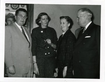 Governor William C. Marland, Ann Hearst, Valena Powell, and Harry Truman are standing in the Hotel Morgan in Morgantown, West Virginia.