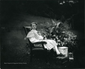 A girl is sitting in a chair outdoors near a large flower bed in Morgantown, West Virginia.