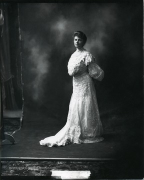A woman poses for a portrait wearing a white dress. 'Source: Hugh Knee.  Knee also worked in New York. These photos may date to that time.'