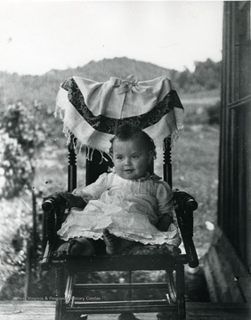 A baby sits in a rocking chair for a picture.