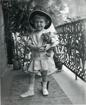 A little girl holds onto her teddy bear in this picture.