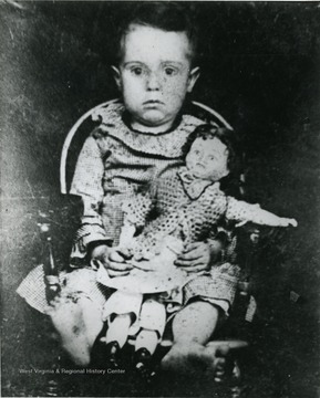 An unidentified child seated in a chair holdind a doll.