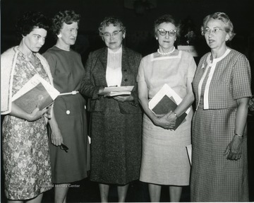 Women standing together holding books and paper. Second from right is Hilda Dailey.