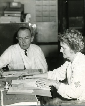 Man with a sling on his arm seated at a table with a health care worker.