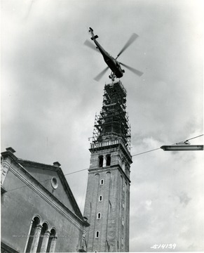 'The 600-pound bronze angel statue is slowly lowered onto the tower of the 175-foot church at Sacile, near Udine by a SETAF H-34 Helicopter of the 202nd Army Aviation Company. The helicopter is piloted by Captain William M. Strawn, Jr, and 1st Lieutenant Ramon F. Warner, while SP2 Richard L. Boyd, inside the craft directed the Army crew and Italian workmen in the delicate task. The 16th Century tower originally bore a wooden angel which was destroyed by earthquake and bombardment. 16 August 1957.' 'Please Credit U.S. Army Photograph.'