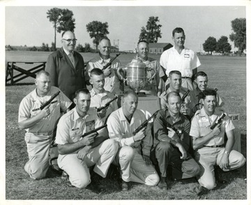 'U.S. International Pistol Team gathered around Mayleigh Challenge Cup. Kneeling from left: CPO D. McCoy, SSgt. Tommy Krumar, Capt. Allyn Clark, John W. Hurst, Stephen G. Webber, SFC Robert E. Monts, SSgt. Larry L. Hausman, MSgt. Roy Ratliff. Standing from left, Charles E. Boomhower, team captain, MSgt. Johnnie M. Martin, SSgt. Albert R. Froede and Dr. Guy C. Davis, team adjutant.' If you want to publish this photograph, please contact the U.S. Army for permission.