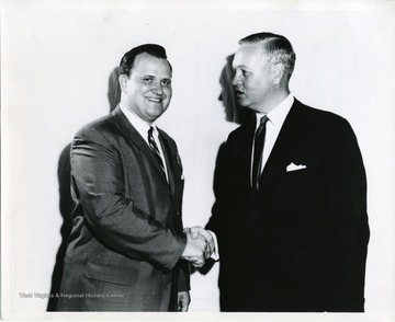 John Pyles is shaking Governor Smith's hand in this photograph.