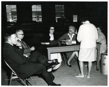 A woman stands in front of the poll workers table.  From left to right: unknown male seated, Donovan Bond, Mrs. Dr. W. Anderson, Mrs. Ben Lynsky, unknown seated, unknown standing.'